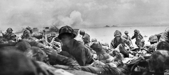 During the invasion of the island of Saipan in the Marianas on June 15, 1944, American Marines stay low and look for shelter from incoming Japanese fire.