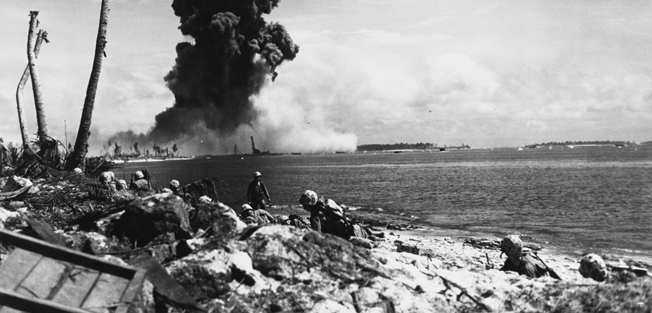 Marines on the island of Roi watch as a Japanese torpedo magazine explodes on the neighboring island of Namur. Marines of the 4th Division under the command of General Harry Schmidt captured the twin islands in early 1944.