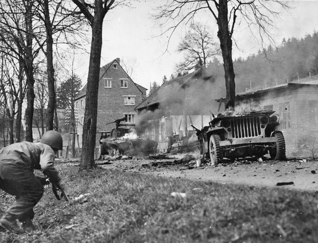 An American soldier cautiously approaches two burning vehicles that had been destroyed by a German ambush. As a scout, Private Sevel never wore equipment or heavy clothing in order to stay mobile on the battlefield.