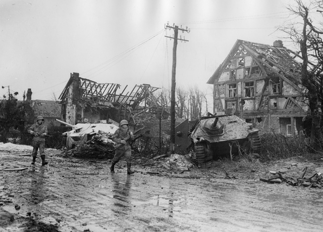 Two American soldiers scout past two German Hetzer tank destroyers. Much of Germany had been blasted to rubble by American air forces.