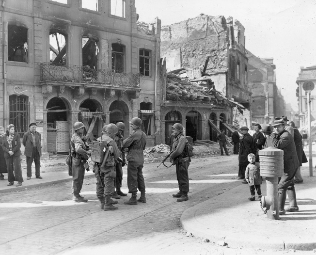 As German civilians look on, soldiers of the 90th Infantry Division's 359th Infantry Regiment discuss their battle plans in the German city of Mainz.