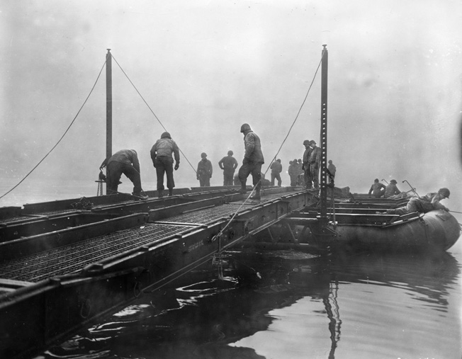 U.S. Army engineers attached to the 90th Infantry Division piece together a Treadway bridge across a German River. When a Messerschmitt fighter plane destroyed a bridge across the Werra River, Private Bernie Sevel found himself stranded on the far side.
