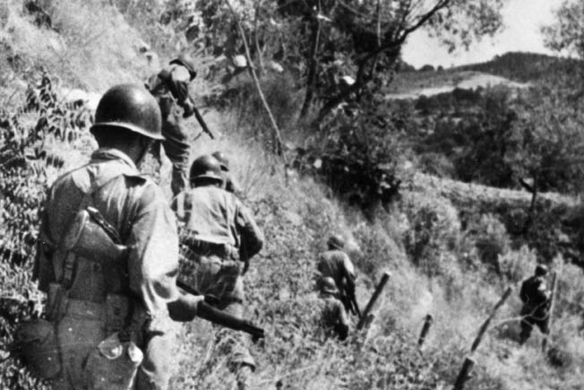 American soldiers patrol along the slope of a vineyard in Sicily during the campaign to capture the island from Axis forces. General George Patton led the American forces in Sicily and did not approve of General Terry Allen's style of command.