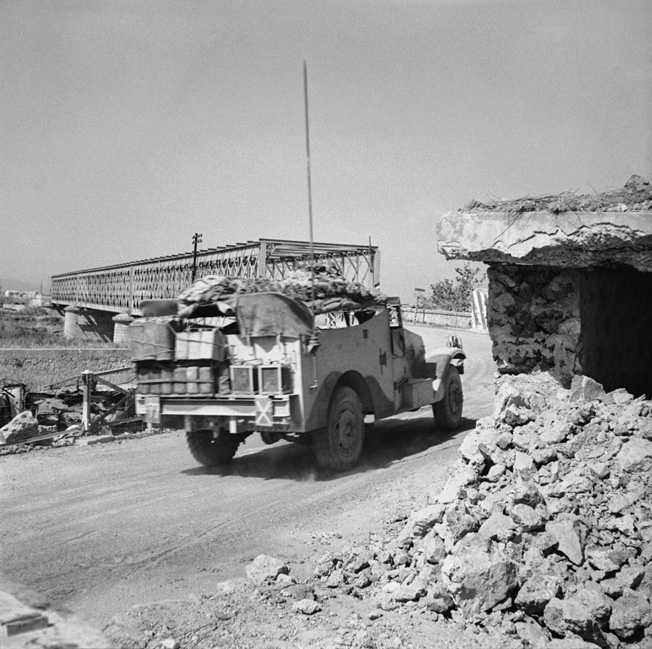WIth the Primosole Bridge (background) now in British hands, a Bren gun carrier heads toward the Catania Plain after the battle.