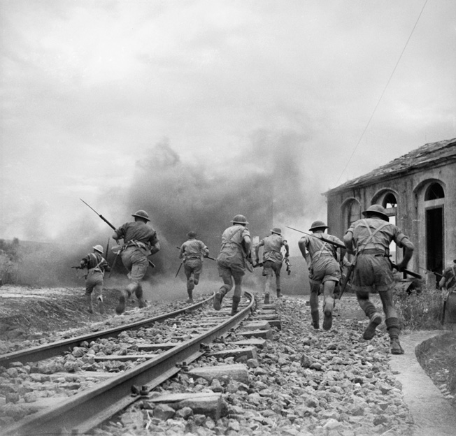 Troops of the 51st Highland Division rush to capture the Sferro railroad station, west of Catania, July 1943. This photo was staged for the photographer after the action.