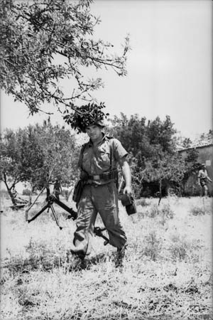 With his helmet well camouflaged, a Hermann Göring Division paratrooper moves to take up a defensive position with his 7.92mm MG 15. The weapon, originally used as an aircraft gun, had a rate of fire of over 1,000 rounds per minute.