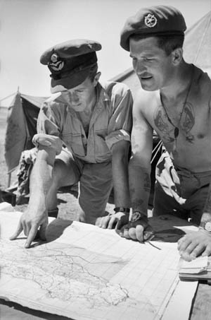 A British RAF tug pilot (left) and the pilot of a glider that he will be towing study a map of Sicily prior to the invasion.