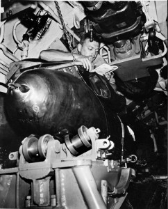 A submarine crewman reads a book in his bunk just a few inches above on the the torpedoes.