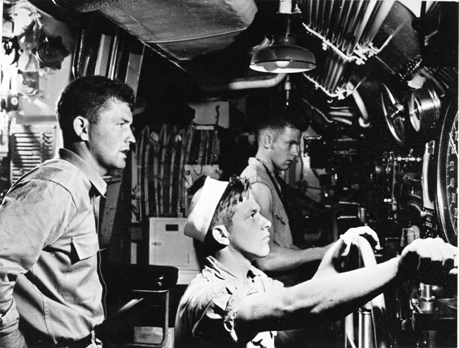 Control room of a submarine. The diving officer (left) is directing the actions of the men at the wheels controlling the stern and bow planes that determine the angle of the dive or resurfacing.