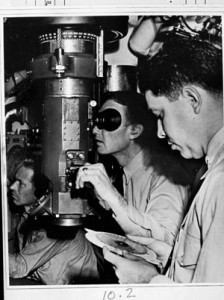 """A submarine skipper uses the periscope to target an enemy vessel while the executive officer (foreground) uses a manual """"Is-Was"""" slide rule computer to target where the target will be, based on where it was and is."""