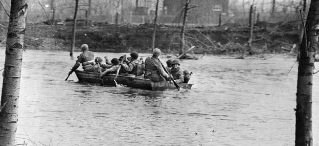 Crossing the rain-swollen Roer River in February 1945, soldiers of the U.S. Ninth Army head toward the front in support of British and Canadian troops who have initiated an offensive that will push the Germans back farther toward Berlin.