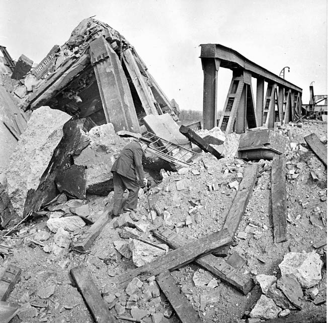 British Prime Minister Winston Churchill climbs across the rubble of a bridge over the Rhine River at Wesel, Germany, on March 25, 1945. As Churchill moved forward, General William Simpson, commander of the U.S. Ninth Army, warned the prime minister that German snipers were still quite active in the area.