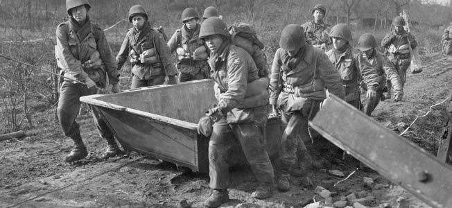 Dragging flat-bottomed assault boats toward the banks of the Roer River on February 23, 1945, engineers of the 84th Infantry Division, Ninth Army, prepare for a contested crossing in less than ideal conditions. Days of rain had turned the Roer into a torrent and prevented units of the Ninth Army from crossing on schedule during the opening phase of Operation Grenade.