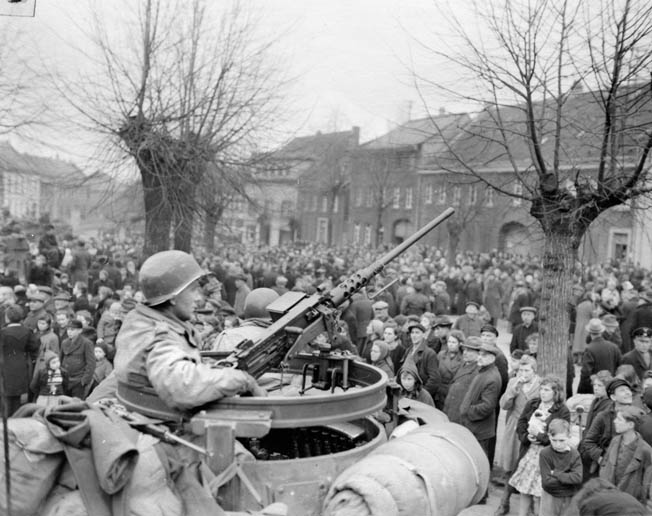 An American tanker of the 2nd Armored Division, Ninth Army, sits in the turret of his tank with a .50-caliber machine gun at his disposal. The soldier watches warily as a throng of curious civilians gathers around in the German town of Juchen, captured by American troops in March 1945.