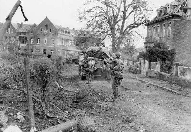 With troops of the U.S. Ninth Army taking cover behind it, a British tank fires on enemy positions in a German town. The U.S. Ninth Army fought under both American and British army group command during the Allied push eastward into Germany.