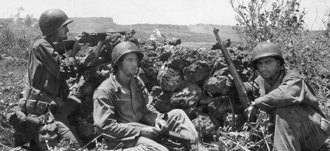 Three soldiers of the 27th Infantry Division take temporary cover from Japanese fire on Saipan. Their vantage point is a rock wall on high ground that overlooks cane fields. The terrain on Saipan contributed to the deliberate progress of the Army troops on the island.