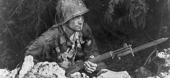 His bayonet fixed to his M1 Garand rifle, a soldier of the 27th Infantry Division peers from cover on the island of Saipan.