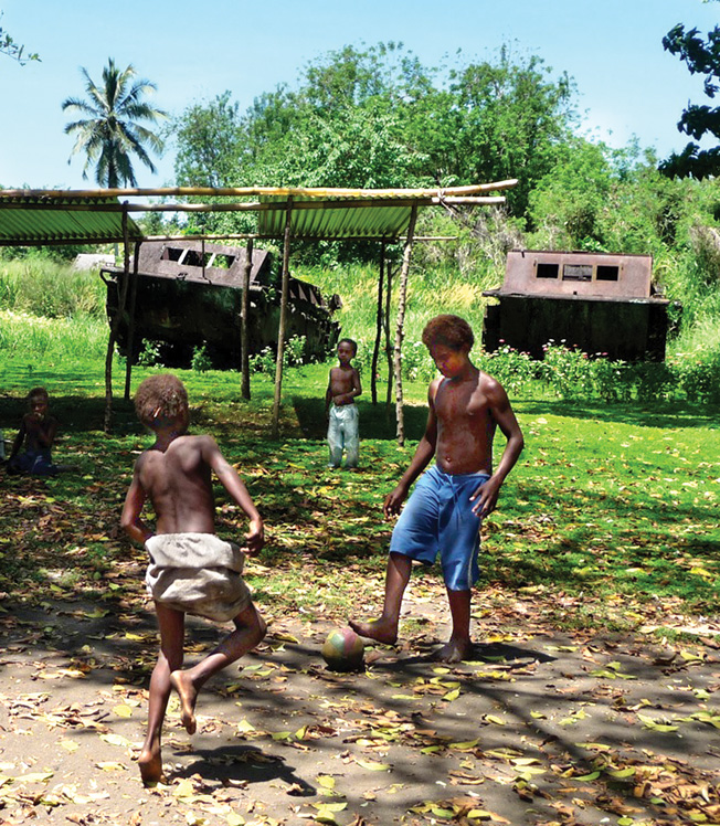 Two of over 70 amtraks left near Red Beach in Tetere appear to stand guard as Solomon Island children play soccer.