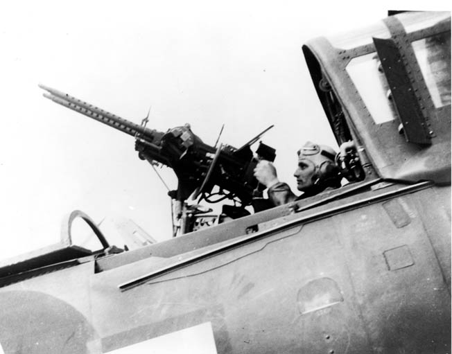 Jim Samar, a radio operator/gunner with dive bombing squadron VB-80, sits in the back seat of a Curtiss SB2C Helldiver and demonstrates taking aim with the twin mounted .30-caliber (7.62mm) machine guns installed to ward off enemy fighter planes.