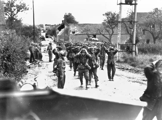 German prisoners of war, lucky to be alive, are marched from St. Lambert-sur-Dives to Trun by men of the 4th Canadian Armoured Division, August 19, 1944.