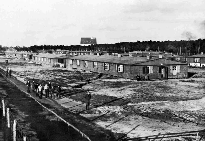 "The Stalag Luft III compound near Sagan, Silesia, with prisoners taking their ""daily constitutional"" along a route inside the barbed wire. This camp was where ""the Great Escape"" occurred in March 1944—before Boam's arrival."