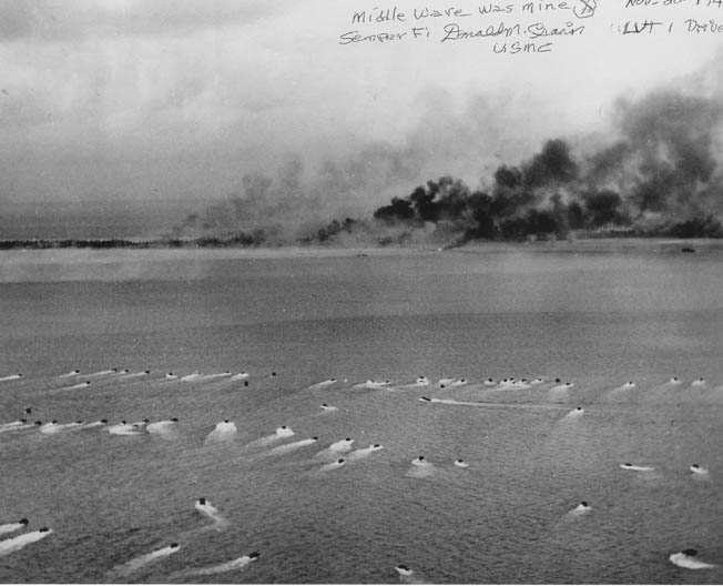 Don Crain's amtrac, churning toward the embattled beach at Betio, was among the group circled in the foreground of this photo. The Japanese took up firing positions on a long pier extending into the lagoon (1) and in the hulk of a half submerged freighter in the shallows near the beach (2). From either of these positions, the defenders raked the approaching Marines with automatic weapons fire.