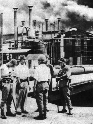 Japanese officers of the 2nd Raiding Regiment and the 229th Infantry Regiment greet one another at the gates of the NKPM oil refinery during the last stages of the conquest of Sumatra. The Japanese coveted the rich natural resources of the Dutch East Indies.