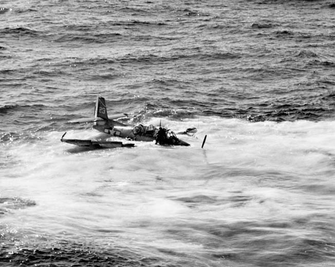 Lieutenant Sevilla climbs out the cockpit as his bomber begins to sink. Another crewman, who escaped through the belly hatch, pops up beneath the ball turret.