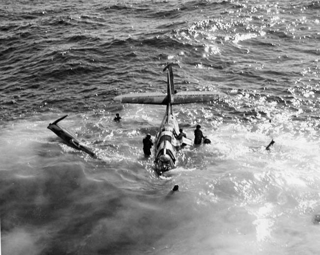 As the TBF sinks deeper, the entire four-man crew safely emerges. One man on the right prepares to unravel an inflatable raft.