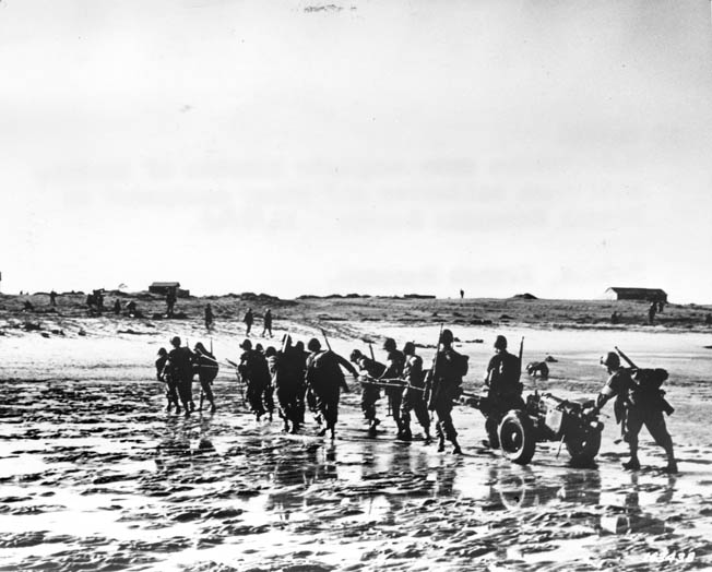 American soldiers drag an antitank gun through the surf on a Moroccan beach on November 8, during the initial landings. The soft sand made beach operations difficult during the first several days of operations.