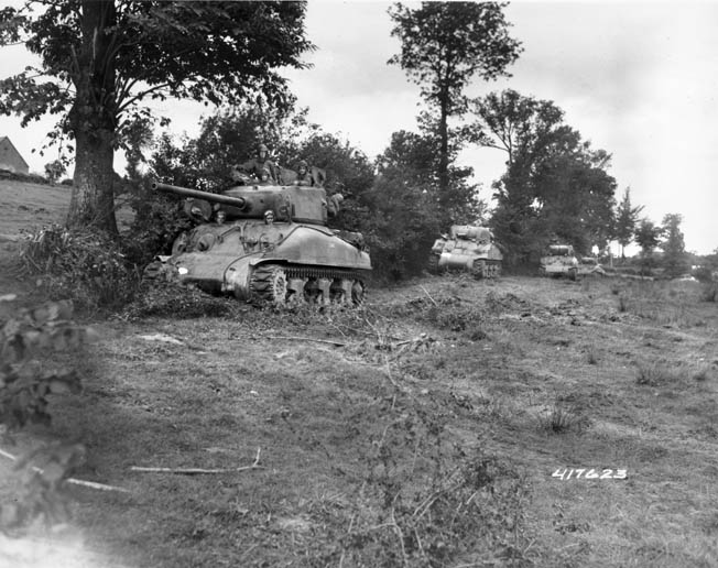 A line of American Sherman tanks hugs a hedgerow in Normandy in the summer of 1944. After the failure of the attack on Hill 192 in June, the men of the 2nd Division trained with armored units to coordinate their attack on July 11.