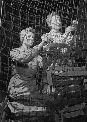 Here, members of the Women's Voluntary Service attach cloth garnish to camouflage netting in 1942.