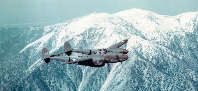 A P-38 flying over mountains.