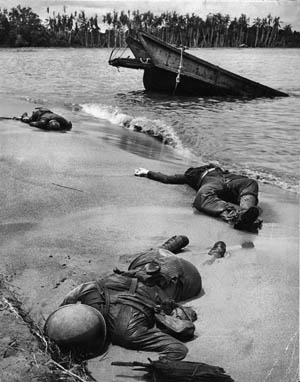 Three dead Americans lie where they fell on the shore near Buna, December 1942. Once thought too graphic, this photo was approved by President Roosevelt for release to the American media nine months later—one of the first published that showed the grim reality of the war.