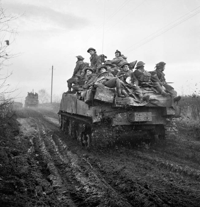 On the move in the vicinity of Geilenkirchen, British soldiers of the 43rd Wessex Division ride atop British tanks. These troops are moving toward German positions in the towns of Tripsrath and Bauchem during an offensive to push the Germans back.