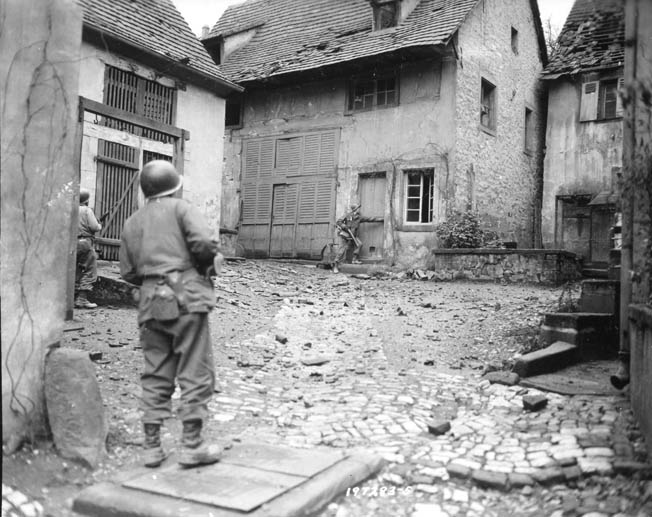 Members of Lt. Col. Felix L. Sparks's 3rd Battalion, 157th Regiment, clear snipers out of buildings in the Vosges Mountain region of France during the U.S. Seventh Army's drive, December 10, 1944.