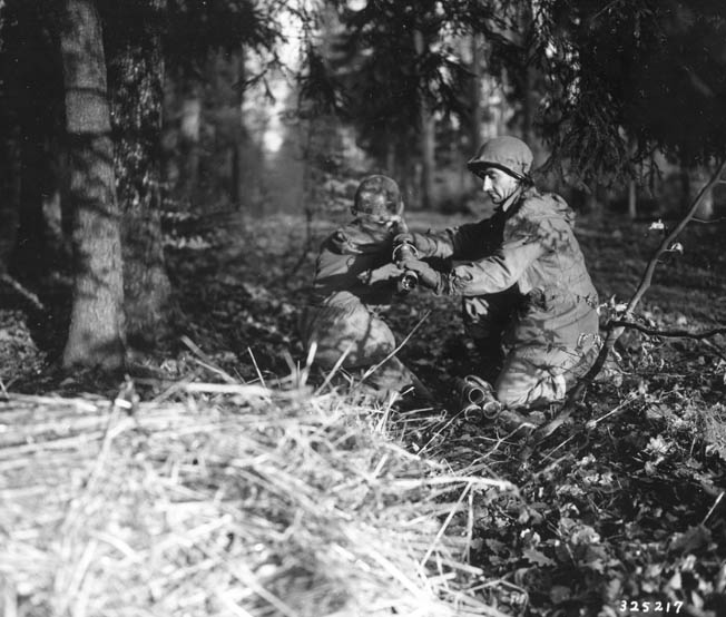 "One member of a 45th Division 3.5-inch rocket launcher (""bazooka"") team loads while the other prepares to fire."