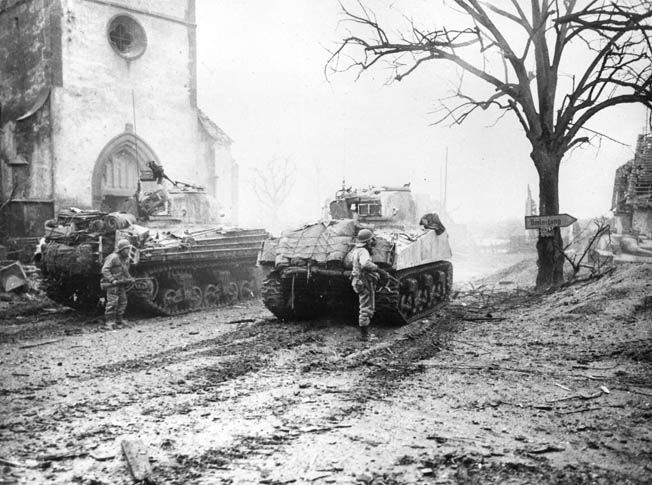 Seventh Army troops advance through a French village behind two M-4 Sherman tanks. Sparks used tanks to his advantage while rescuing his troops north of Reipertswiller, January 1945.