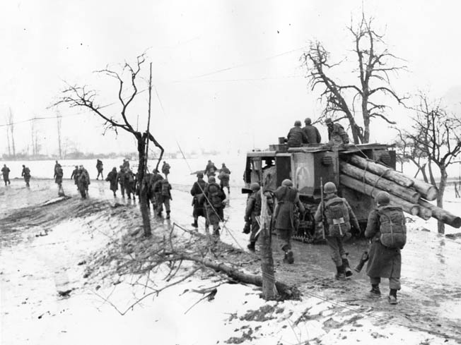 U.S. Seventh Army soldiers, accompanied by an M-4 high-speed tractor, move down a wet, snowy road in northeastern France.