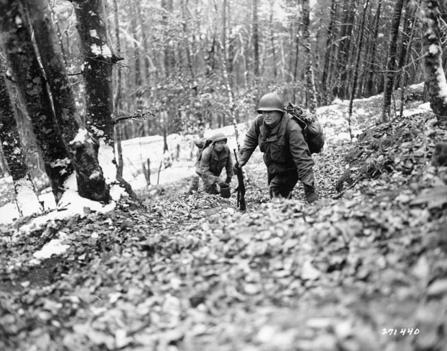 Men of a 157th Regiment pioneer squad carry rations and supplies up difficult terrain to men in foxholes in the snowy Vosges Mountains.