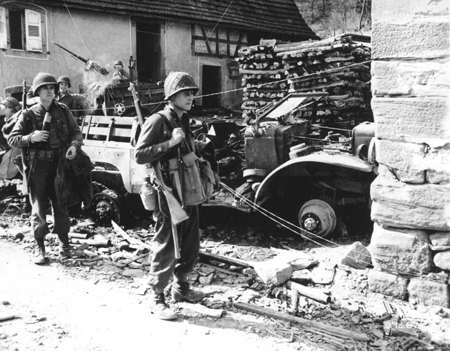 American troops pass a destroyed weapons carrier in Reipertswiller on their way into Germany. The little-known battle was a drama of courage, misery, and struggle that cost more lives than it was perhaps worth.