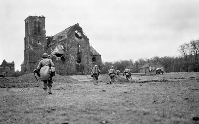 104th Division troops advance past a bombed-out cathedral in Eschweiler, a few miles east of Aachen, on their way to Weisweiler. Creamer was appalled by the destruction he saw—and caused.