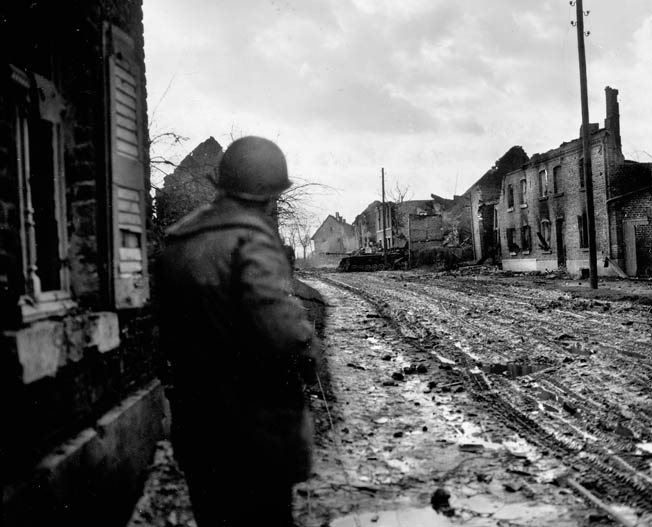 A soldier from the 104th cautiously advances toward a knocked-out panzer sitting in the middle of Lamersdorf. The town had been heavily shelled by American artillery before the 104th seized it. Creamer said he was frightened by a King Tiger tank in the nearby town of Lucherberg.