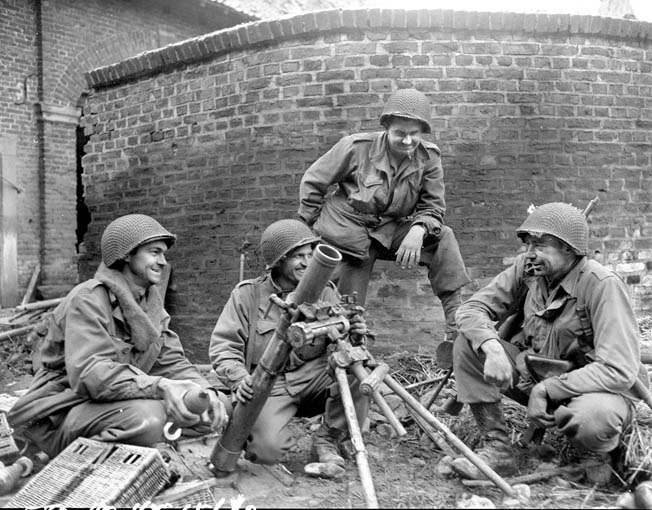 A 104th Division mortar crew smiles as they pose around a captured German 81mm mortar they used against the enemy near Duren, Germany.