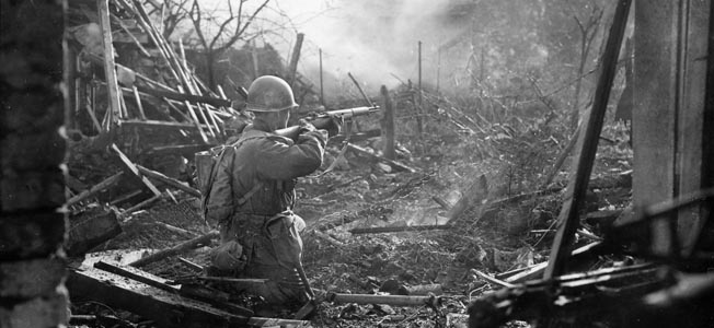 During the drive across northern Germany, a Timberwolf rifleman fires his M-1 Garand toward Germans in a burning building in Eschweiler, late November 1944.