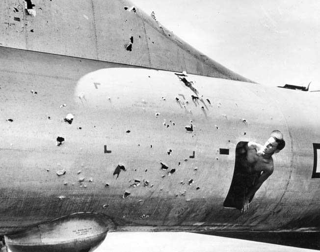 A crew member surveys the damage to his B-29 caused by Japanese flak guns during an April 1945 raid on the Japanese capital.