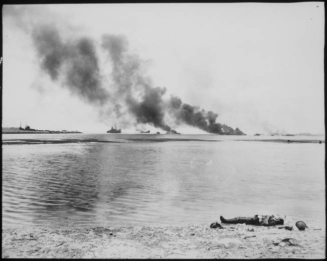 A Japanese soldier lies dead at the water's edge in Tanapag harbor on the island of Saipan, July 15, 1944. This soldier was among a number of Japanese troops that sought safety aboard ships in the harbor. Several of those vessels were attacked by U.S. aircraft and blaze in the distance.