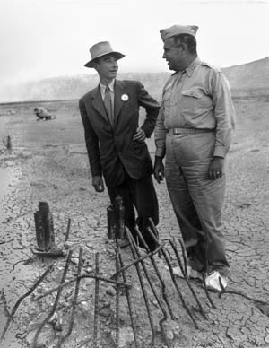 In September 1945, physicist J. Robert Oppenheimer (left) and Groves (right) survey the twisted steel remnants at the site of the Trinity atomic bomb test detonation two months earlier.