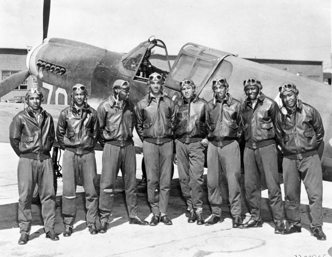 "A group of Tuskegee Airmen pilots of the 99th Pursuit Squadron, posing next to a P-40 ""Warhawk,"" distinguished themselves in aerial attacks against Pantelleria."