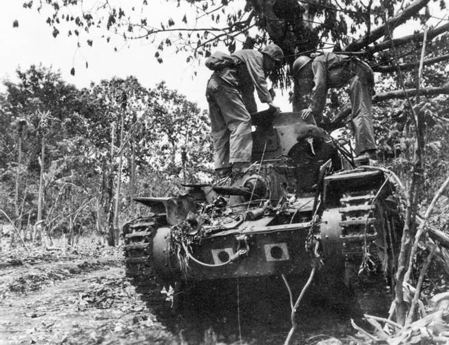 Marines inspect a knocked-out Type 95 Ha-Go light tank.